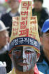 Unionised worker wearing mourning clothes takes part in May Day rally denouncing Lee government's economic policies in Seoul