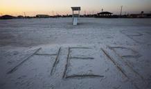 Alguien escribió la palabra «Ayuda» en esta playa de Alamaba, una apropiada estampa para la situación de una zona que se verá muy afectada.