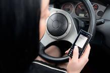 Una conductora escribe un mensaje de texto de móvil mientras conduce