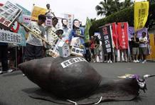 """Activistas junto a la escultura de un caracol en la que se puede leer: """"Quiero vivienda social"""", durante la manifestación del 1º de Mayo en Taiwan"""