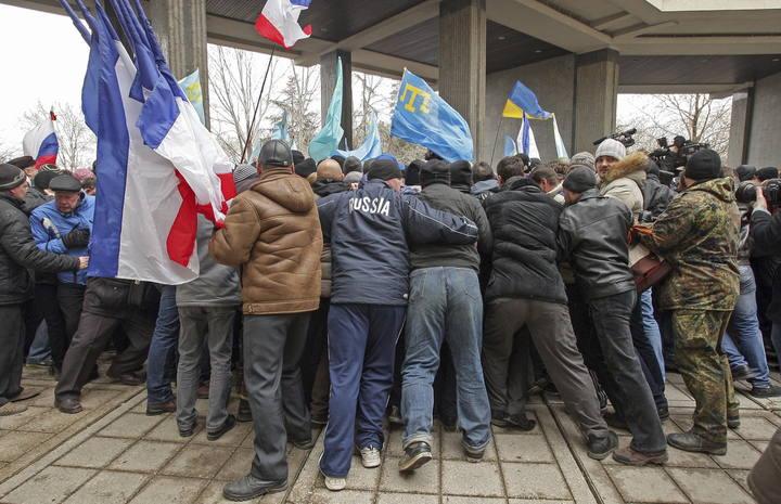 Activistas prorrusos empujan a manifestantes tártaros partidarios de la unidad con Ucrania en Simferopol, capital de Crimea