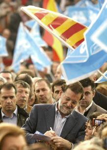 El presidente del PP, Mariano Rajoy (c), firma un autógrafo a su llegada a la plaza de toros de Zaragoza.