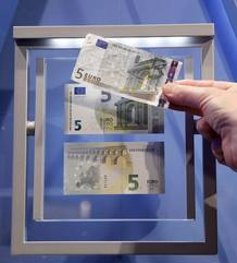 A journalist compares the new 5 euro note with an old one (top) during a ceremony with Draghi, President of the European Central Bank (ECB), in Frankfurt