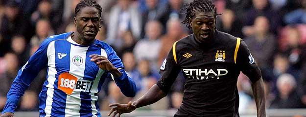 El delantero togolés del Manchester City Emmanuel Adebayor lucha por el balón con el holandés Mario Melchiot, del Wigan.