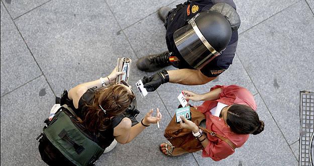 Un agente de Policía requiere la documentación a dos mujeres en un acceso a la Puerta del Sol de Madrid