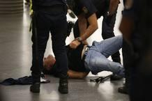 Agentes de policía detienen a uno de los miembros del piquete informativo en Atocha