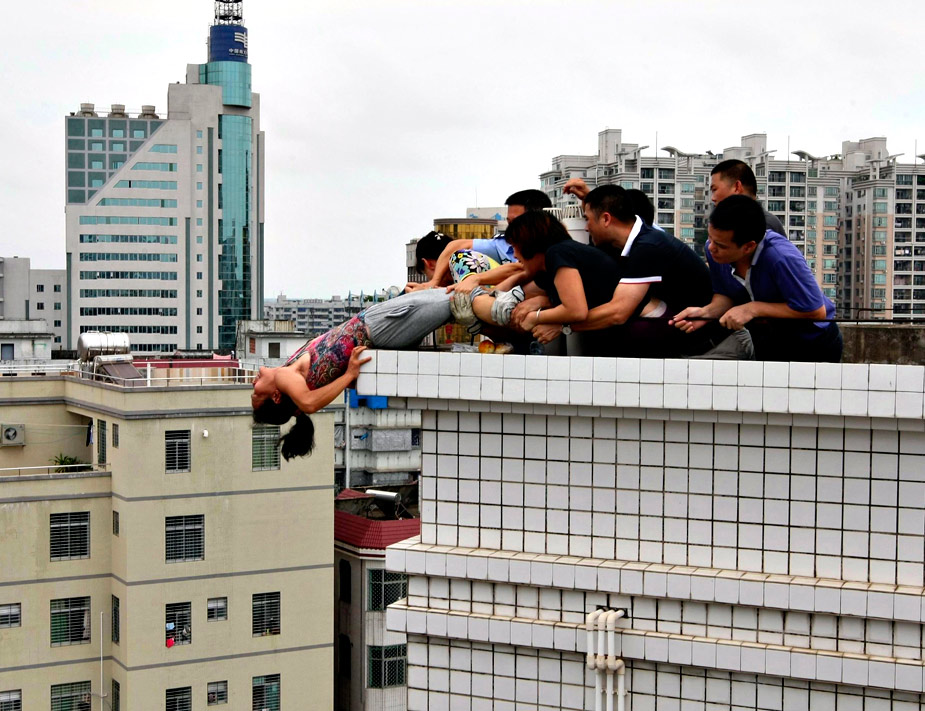 En agosto fue tomada esta impactante instantánea de una mujer suicida que intentaba arrojarse de un edificio en China, en la provincia de Guangdong, ante los denodados esfuerzos de sus familiares y del equipo de emergencia por impedírselo. REUTERS