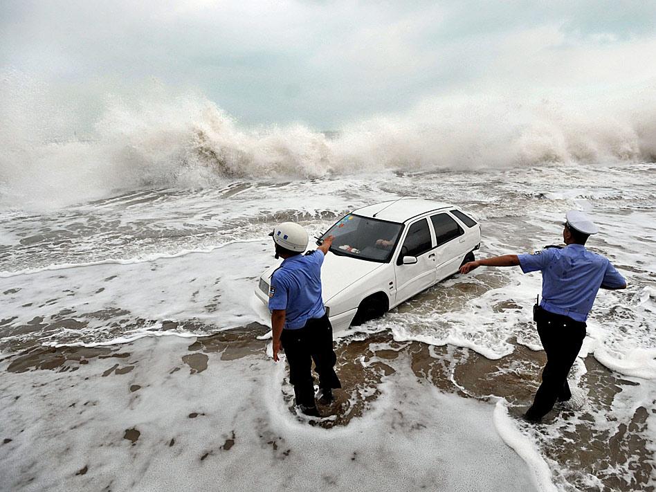 En agosto, el tifón Bolaven sacudió el nordeste de China y algunos policías, como estos de la provincia de Shandong, se afanaron en ordenar la circulación, incluso entre olas.