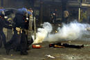 Riot police storm past a dead protestor who has been shot and killed by Carabiniere during rioting in central Genoa