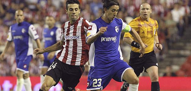 El capitán del Hapoel Kiryat Shmona FC, Adrian Rochet disputa un balón con el delantero del Athletic Club de Bilbao Markel Susaeta.
