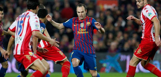 Barcelona's Iniesta is challenged by Sporting de Gijon's players during their Spanish first division soccer match at the Nou Camp stadium in Barcelona