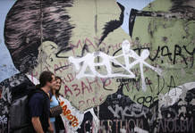 Tourists walk past the East Side Gallery in Berlin