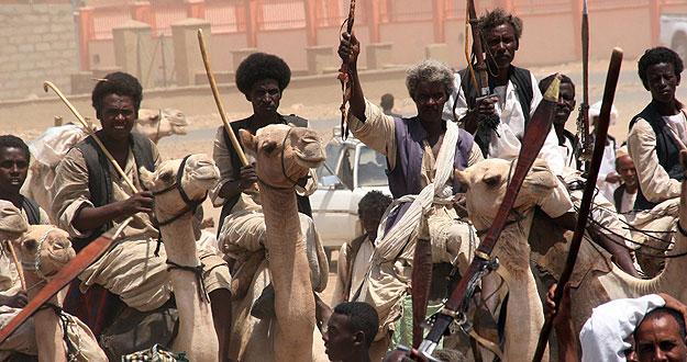 Un grupo de hombres montados en camellos da la bienvenida al presidente de Sudán Omar Hassan al-Bashir durante su visita a la ciudad de Sinkat.
