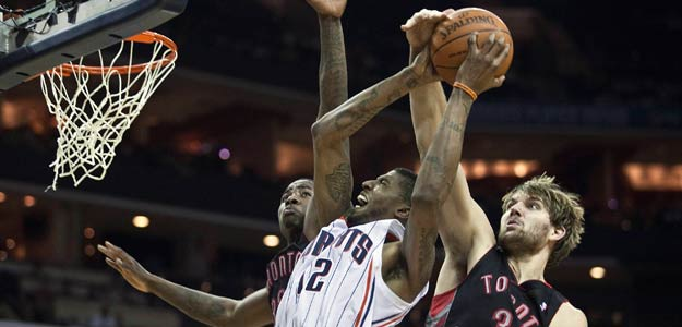 Charlotte Bobcats' Thomas goes up for a layup against Toronto Raptors' Gray and Davis during an NBA basketball game in Charlotte