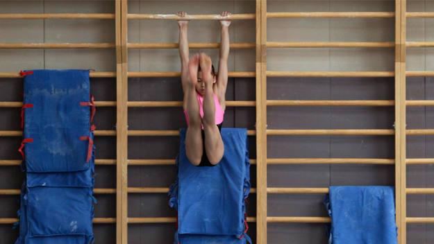 Gimnasta practicando uno de sus entrenamientos en un centro deportivo en China.