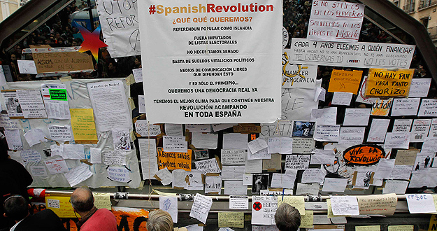 People look at signs put up by demonstrators in Madrid's Puerta del Sol