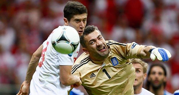 El delantero polaco Robert Lewandowski (L) intenta marcar al meta griego Kostas Chalkias en el primer partido
