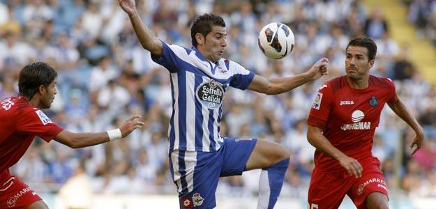 """El delantero del Deportivo Iván Sánchez-Rico """"Riki"""" (c), lucha la pelota con el centrocampista del Getafe CF, Xavi Torres (d)"""