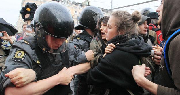 Unos policías antidisturbios forcejean con unos manifestantes que participan en una protesta no autorizada en el centro de Moscú.