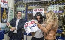 El dueño de la administración de lotería de Sanlúcar la Mayor, donde ha tocado el Gordo, descorcha una botella de champán, junto a sus empleadas.