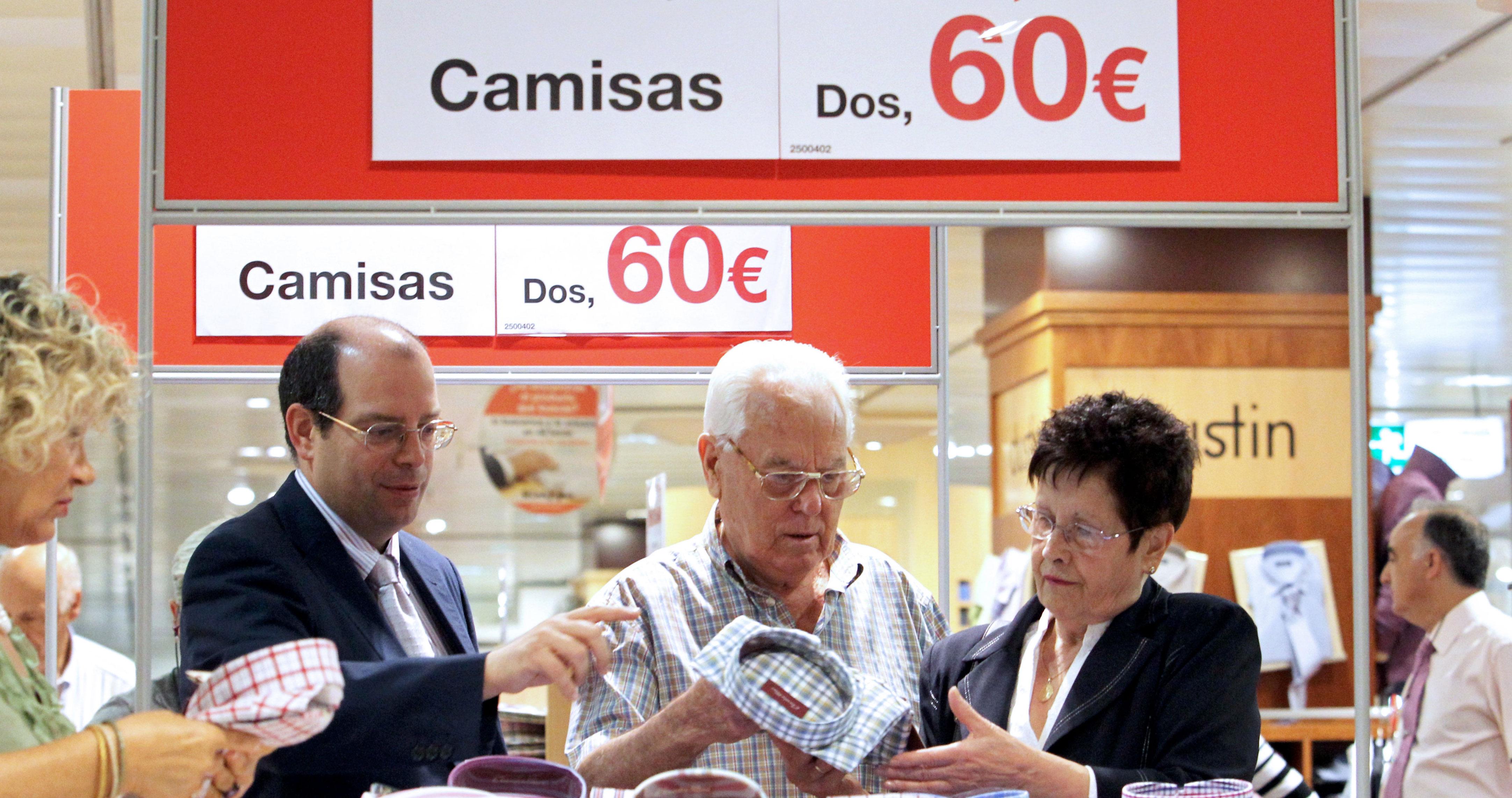 Un empleado de un centro comercial de Bilbao atiende a un matrimonio en la sección de camisería en el primer día de rebajas.