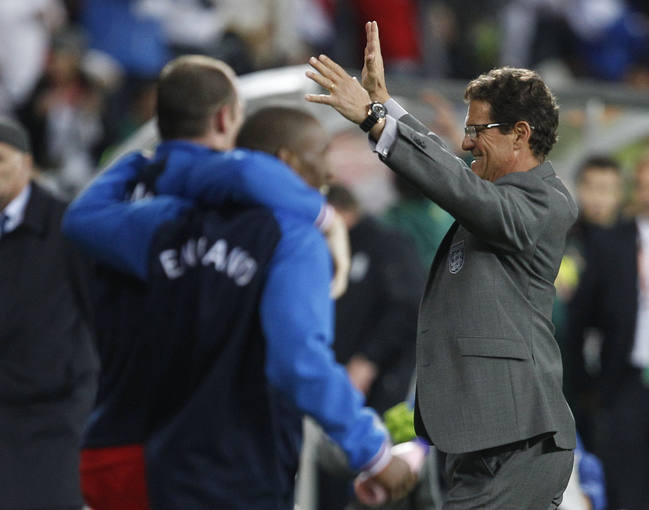 England's coach Fabio Capello celebrates with the team after their 2010 World Cup Group C soccer match against Slovenia in Port Elizabeth