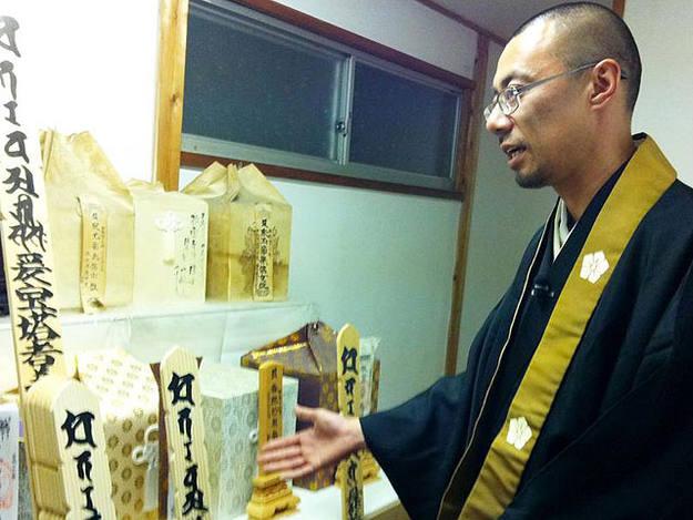 Este monje muestra las cajas con cenizas de vecinos muertos en el tsunami. Vela por sus almas.