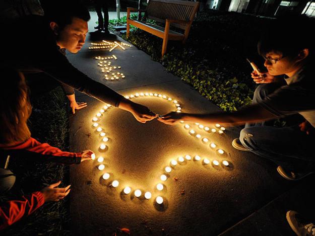 Estudiantes dibujan con velas el logo de Apple