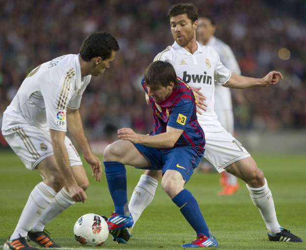 El delantero argentino del FC Barcelona Lionel Messi (c), pelea un