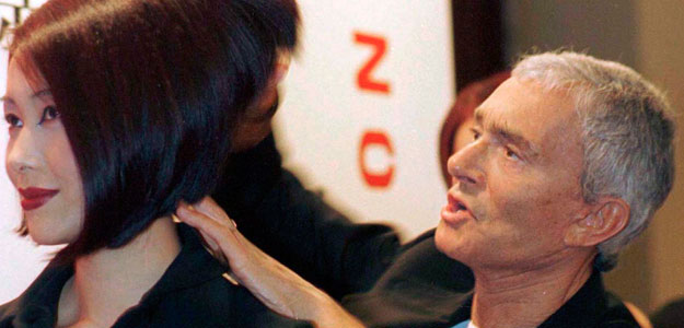 File photo of famed hairdresser Vidal Sassoon helping to style the hair of a model in Shanghai
