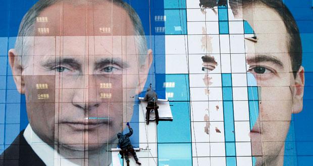 Operarios retiran un cartel prelectoral de Medvédev y Putin en las elecciones legislativas de 2011.