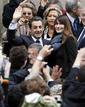 France's President and UMP party candidate for the 2012 French presidential elections Nicolas Sarkozy arrives with France's first lady Carla Bruni-Sarkozy at a voting station in Paris