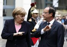France's President Hollande listens to Germany's Chancellor Merkel as they attend the 50th anniversary ceremony of a reconciliation meeting in Reims