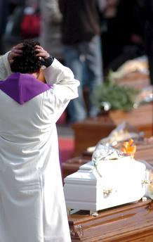 Un sacerdote se emociona ante la visión de un pequeño ataúd en L'Aquila.