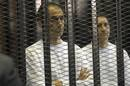 Gamal and Alaa, sons of former Egyptian President Mubarak, stand inside a cage at a courtroom in Cairo