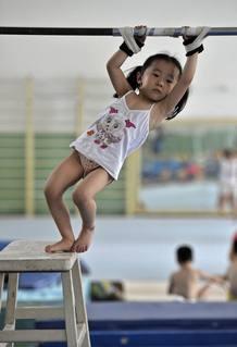 Una niña del equipo de gimnasia infantil de Nanjing, China, con las manos atadas en la barra horizontal, preparándose para su entrenamiento deportivo.