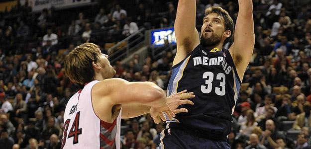 El jugador de los Grizzlies de Memphis Marc Gasol lanza el balón ante la presión de Aaron Gray de los Raptors de Toronto.