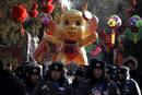 Security guards and police march past a large dragon doll before the opening of the temple fair at Ditan Park in Beijing