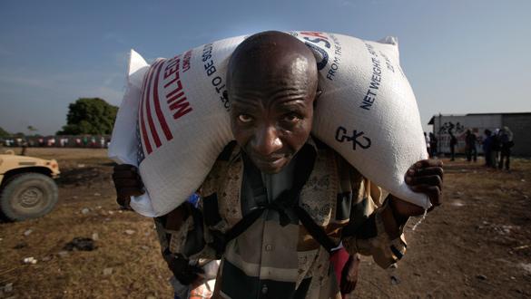 Un haitiano lleva un saco de arroz distribuido por las agencias de ayuda en Puerto Príncipe.