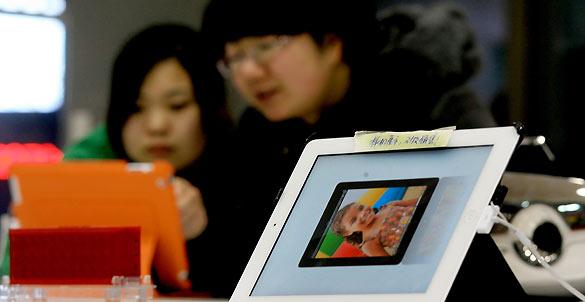 Dos clientes prueban un iPad en una tienda en Dalian, al noreste de China
