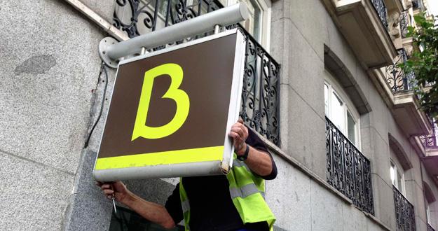 Un hombre coloca el logo en una sucursal de Bankia