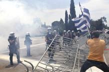Un hombre ondea una bandera griega ante la Policía antidisturbios