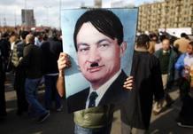 Un hombre porta una foto del presidente egipcio, Hosni Mubarak, con un bigote dibujado al estilo de Hitler. (31/1/2011).