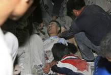 Un hombre trata de salir de entre los escombros de una escuela de Sichuan