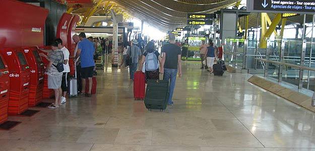 Dos pasajeros se dirigen hacia el mostrador de facturación en Barajas