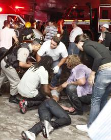 A policeman and rescues workers help a man in front of the Kiss nightclub in the southern city of Santa Maria