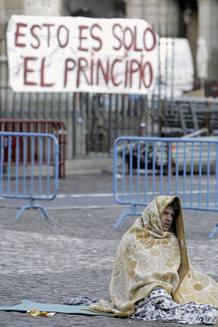 """Un """"indignado"""" en la Plaza Mayor de Madrid, después de que unos treinta de ellos pasara la noche en el lugar, poco antes de ser desalojados por la Policía Municipal, que les obligó a retirarse a la calle de Toledo"""