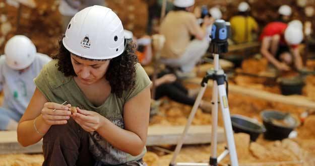 Una joven examina un fragmento de roca en las excavaciones de verano en el yacimiento de Atapuerca.