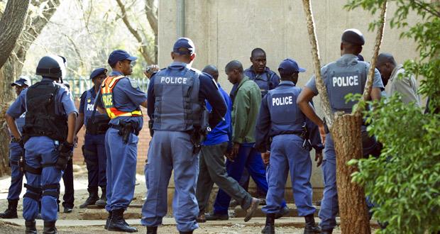 La policía custodia a los mineros detenidos tras el enfrentamiento que acabó con la vida de 34 de sus compañeros.