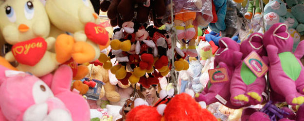 A man looks for Christmas gifts inside a toy stall along a street in Manila